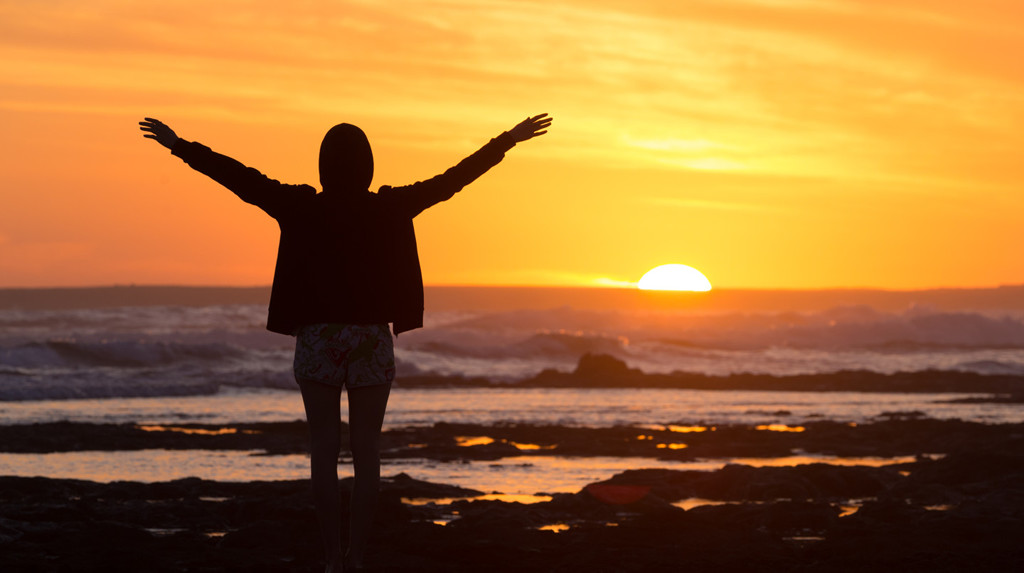 Functional Medicine - Overcome Disease - Sunset - Free woman enjoying freedom on a beach